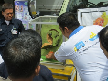 Workshop facilitator from SEEDS Asia explaining the mechanism of landslides using instructional materials in their Mobile Knowledge Resource Center (MKRC)
